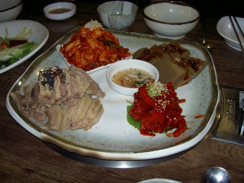"tarting from the bottom left and going clockwise:  bo-ssam, kimchi (fermented spicy cabbage, probably the most famous Korean dish), dotori mook (acorn ""jello"" - that's the only way I can describe it), and spicy-seasoned fish"